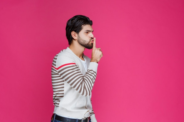 Homme faisant signe de main de pistolet ou de silence de profil.