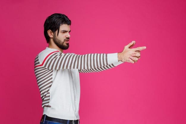 Homme faisant le symbole du pistolet dans la main.