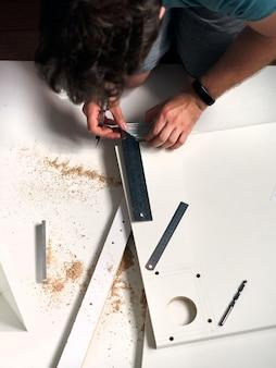 Homme faisant des travaux de rénovation à la maison, mesurant un morceau de bois
