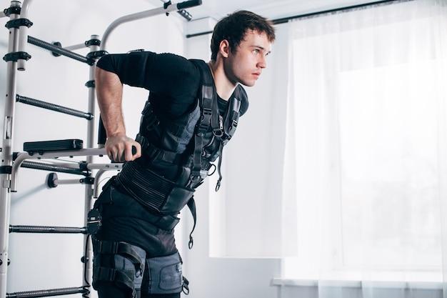 Homme faisant des trempettes triceps sur des barres parallèles