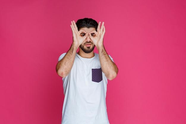 Homme faisant le visage de hibou avec ses mains.