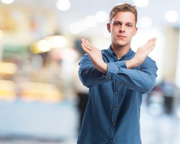 Homme faisant un x avec sa main