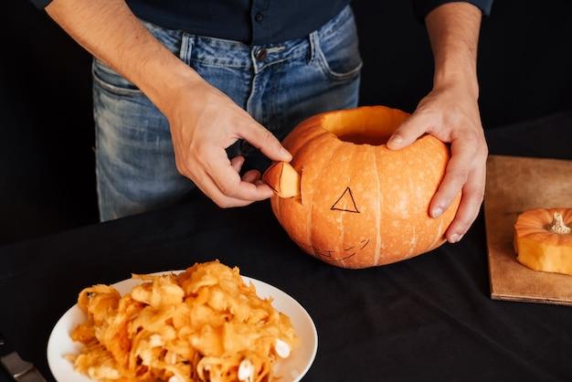 L'homme fait une citrouille orange pour halloween
