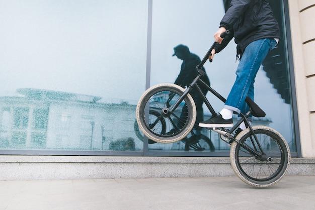 Un homme fait du vélo sur la roue arrière d'un bmx contre une vitrine en verre. un adolescent fait des tours sur un vélo bmx