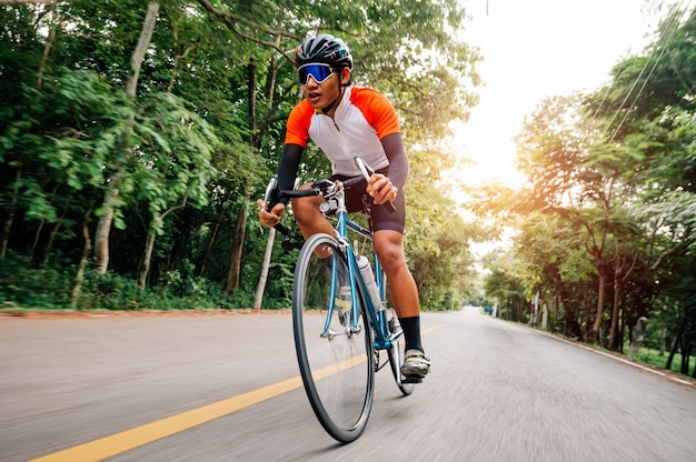 Un homme fait du vélo sur la route. homme monté sur un vélo de sport vintage pour l'exercice du soir. un homme fait du vélo pour respirer l'air frais au milieu de la nature, d'un pré, d'une forêt, avec le soleil du soir qui brille à travers