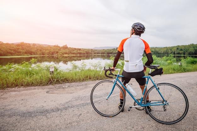 Un homme fait du vélo sur la route. homme monté sur un vélo de sport vintage pour l'exercice du soir. un homme fait du vélo pour respirer l'air frais au milieu de la nature, des rivières, de la forêt, avec le soleil du soir qui brille à travers