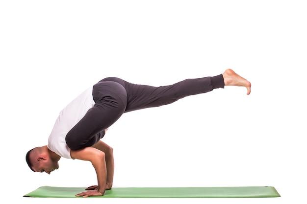 L'homme fait du yoga isolé sur fond blanc