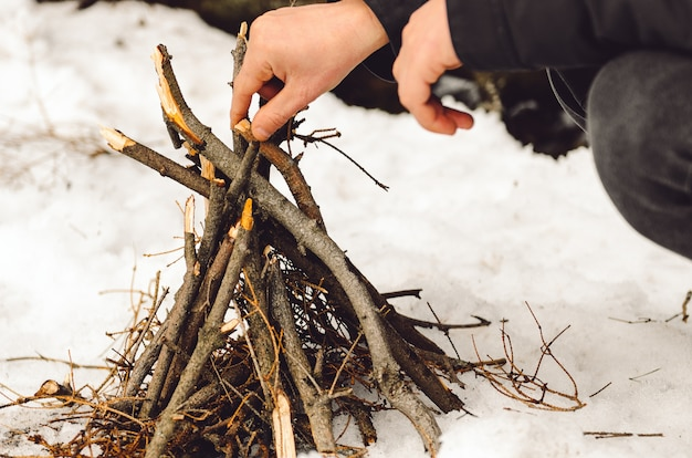 Un homme fait un feu de camp en hiver lors d'une randonnée.