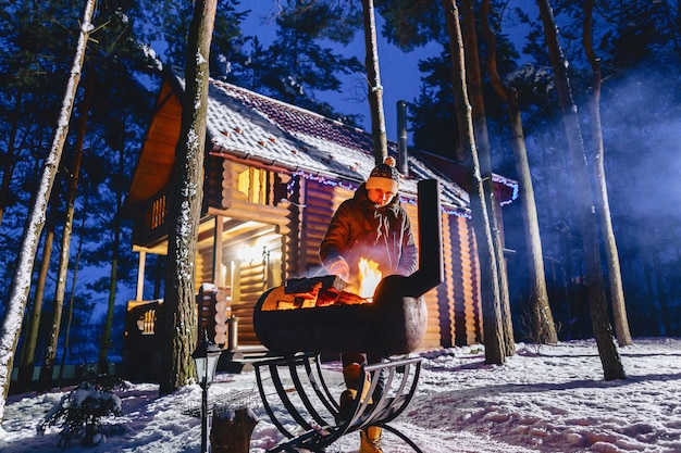 Un homme fait frire de la viande grillée contre le chalet le soir et dans la fumée