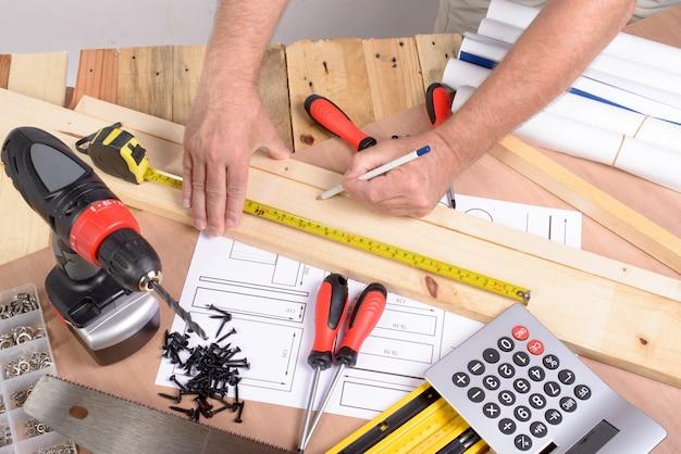 Un homme a fait un meuble avec divers outils de menuiserie