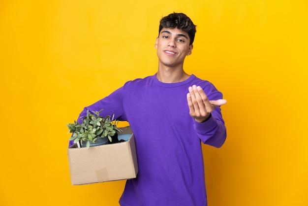 L'homme fait un mouvement tout en ramassant une boîte pleine de choses invitant à venir avec la main. heureux que tu sois venu