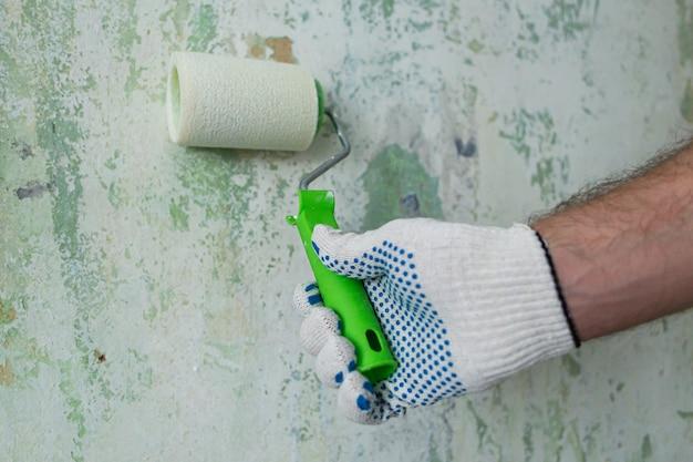 Un homme fait des réparations, peint un mur