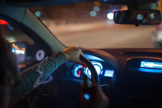 L'homme fait des ronds de fumée dans la voiture. le soir la nuit