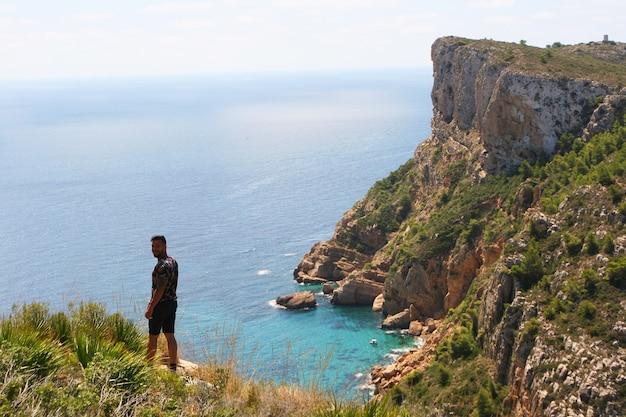 Homme sur une falaise face à la mer