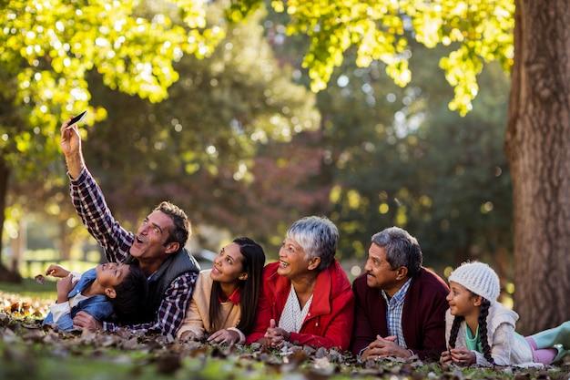 Homme avec famille prenant selfie au parc