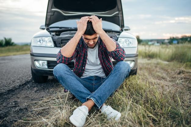 Homme fatigué assis sur un pneu, voiture cassée