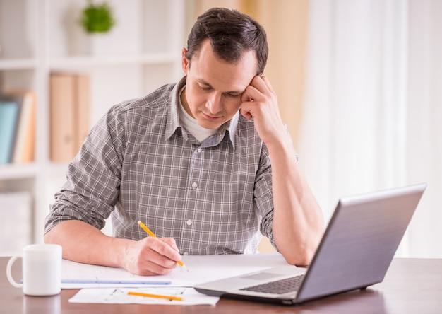 Homme fatigué, assis à table avec ordinateur portable et travaillant.