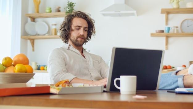 Homme fatigué attrayant travaillant avec un ordinateur portable de la maison. l'homme assis à la table mange une pizza pendant le travail à distance à domicile. jeune homme avec des poils assis et met ses jambes sur la table dans une cuisine confortable.