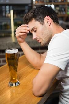 Homme fatigué ayant une bière