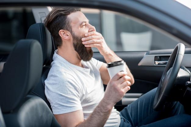 Homme fatigué bâillant sur le siège avant de la voiture tenant un café pour aller