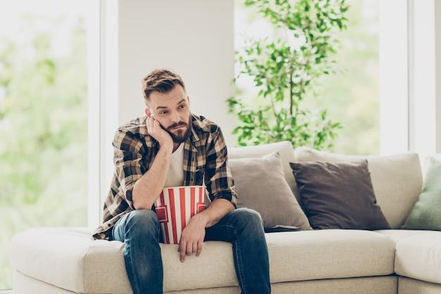 Homme fatigué barbu en chemise à carreaux et jeans en denim s'ennuyer