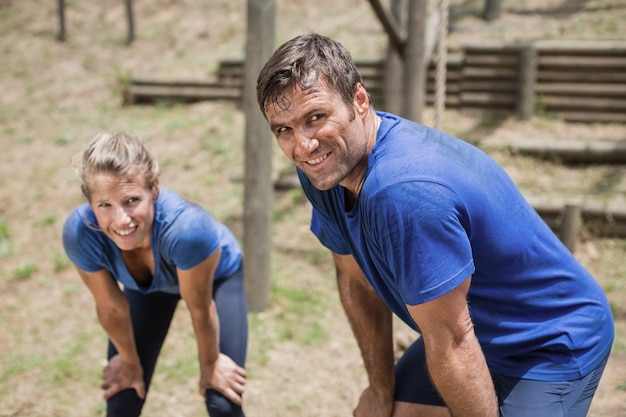Homme fatigué et femme se pencher avec les mains sur les genoux pendant la course d'obstacles dans le camp d'entraînement