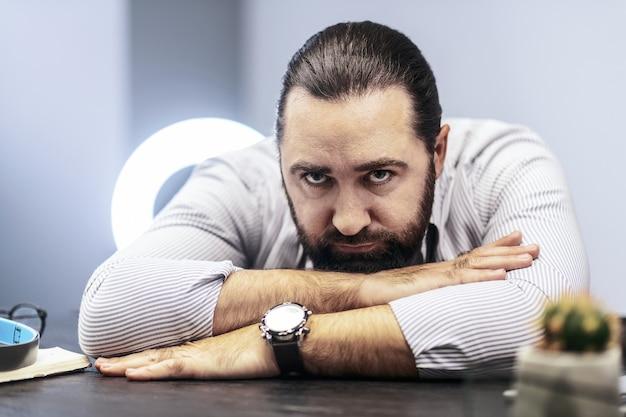 Homme fatigué. homme barbu aux cheveux noirs portant une chemise rayée à la fatigue