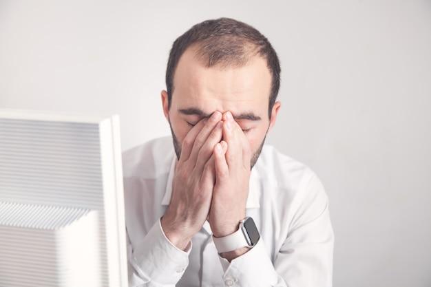 Homme fatigué de race blanche au bureau.