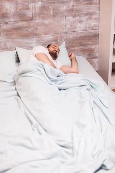 Homme fatigué se reposant sous la couverture dans son lit confortable la nuit