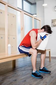 Homme fatigué avec une serviette sur le visage, assis dans le vestiaire