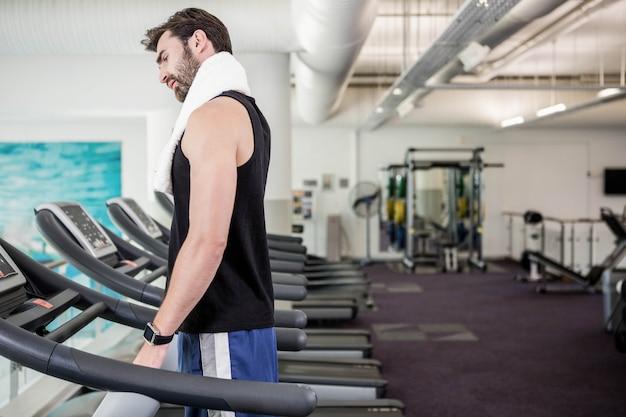 Homme fatigué sur tapis roulant à la gym