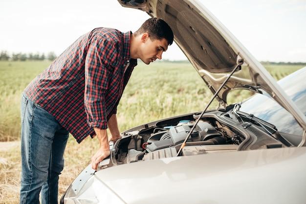 Un homme fatigué tente de réparer une voiture cassée