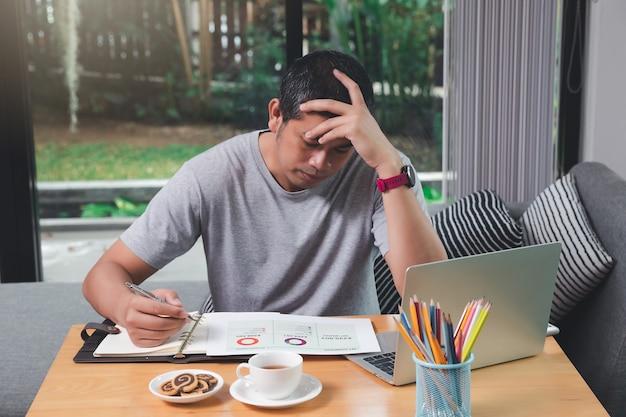 Homme fatigué travaillant à la maison avec des crayons, du café et une collation