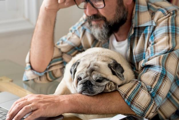 Homme fatigué travaille à la maison sur un ordinateur portable dans l'emploi moderne numérique en ligne