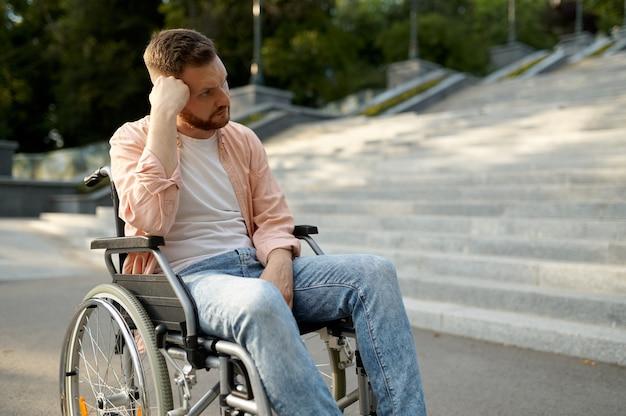 Homme en fauteuil roulant dans les escaliers, problème de handicap