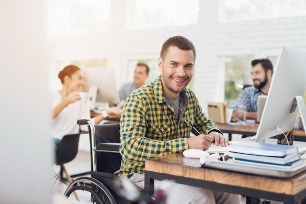 Un homme en fauteuil roulant écrit avec un stylo dans un cahier.