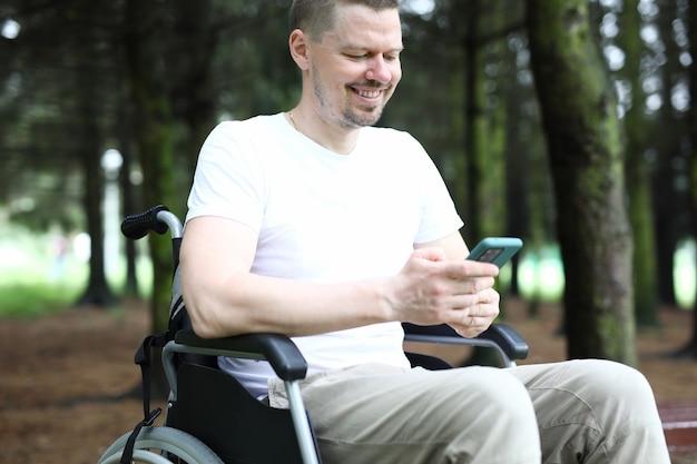 L'homme en fauteuil roulant est assis tenant le smartphone dans sa main et sourire