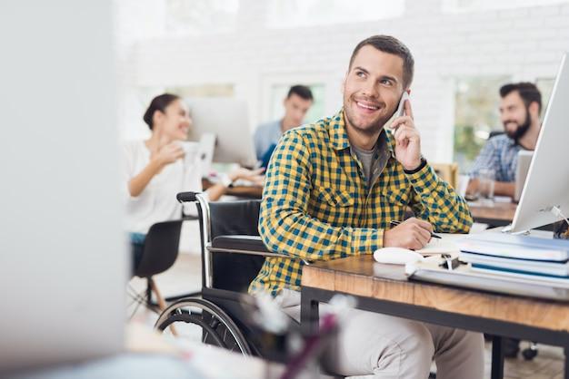 Un homme en fauteuil roulant rédige des notes et parle au téléphone