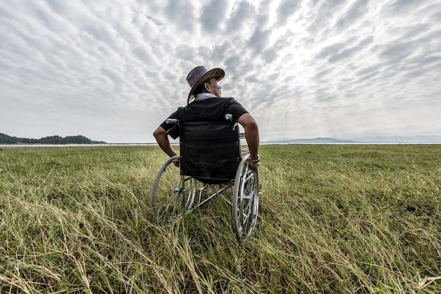 Homme sur un fauteuil roulant se détendre dans un parc