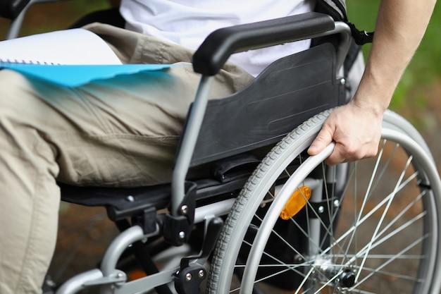 L'homme en fauteuil roulant tient la roue avec sa main