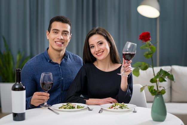Homme et femme acclamant leur dîner romantique
