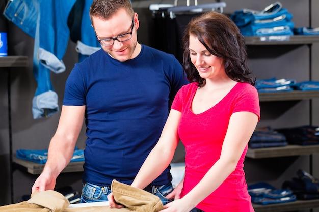 Homme et femme achète des jeans dans la boutique