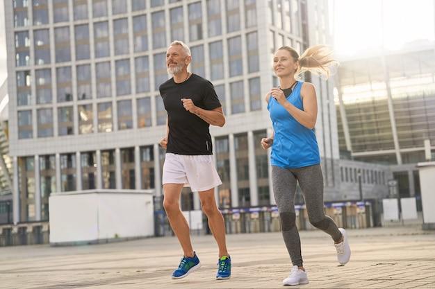 Homme et femme actifs d'âge moyen faisant du jogging ensemble le matin tout en s'entraînant à l'extérieur