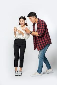 L'homme et la femme adorent écouter de la musique sur leurs smartphones