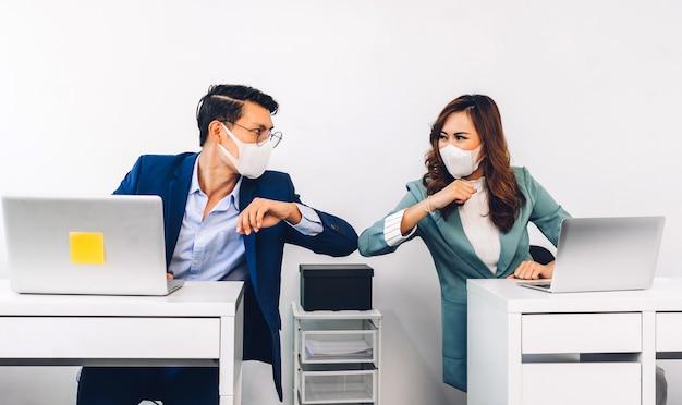 Homme et femme d'affaires asiatiques avec masque facial et coudes avec imprimantes au bureau