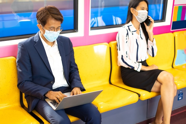 Homme et femme d'affaires asiatiques portant des masques faciaux pendant la pandémie de covid-19 lors de leurs déplacements en transports en commun
