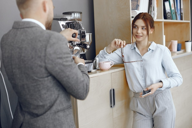 Homme et femme d'affaires au bureau. pause café dans le couloir de la grande entreprise.