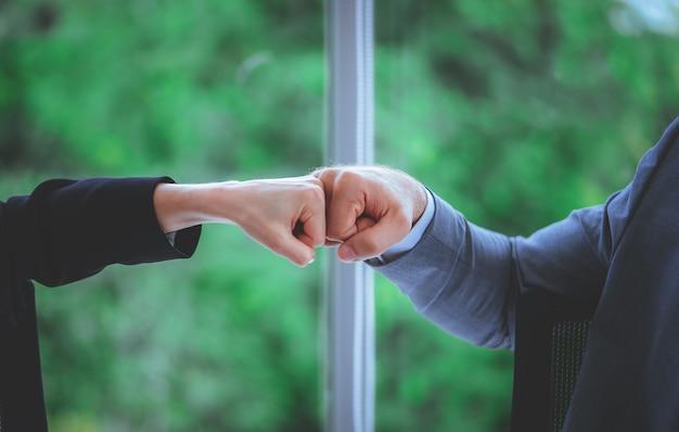 Homme et femme affaires couple d'affaires poing bosse main ensemble pour travail d'équipe