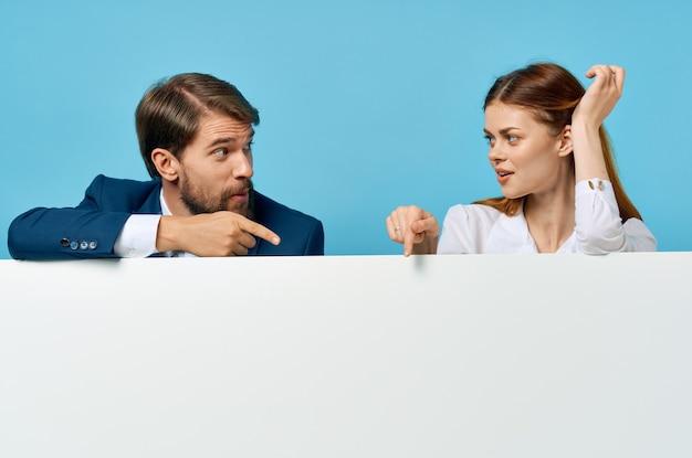 Homme et femme d'affaires avec fond bleu de panneau publicitaire d'affiche de maquette blanche