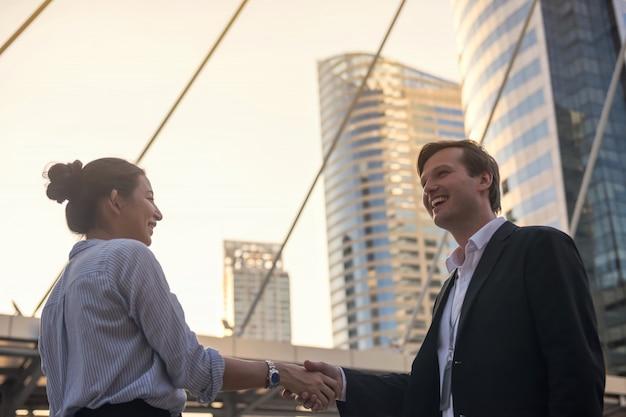 Homme et femme d'affaires se serrent la main en ville
